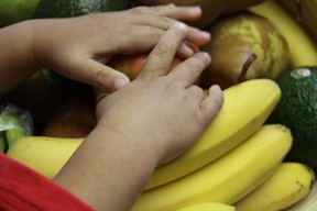 Hands Reaching for Fruit Including Bananas