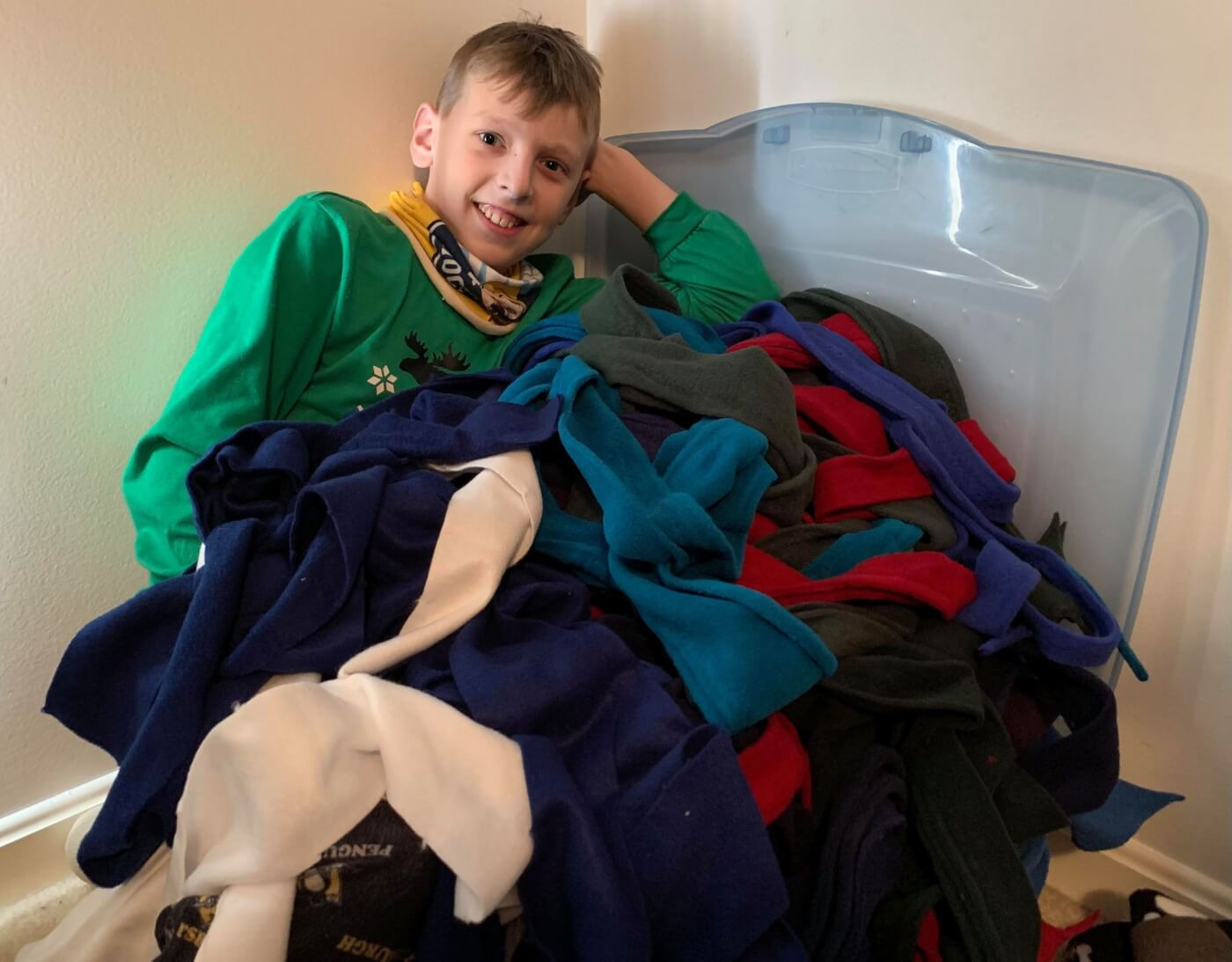 ryan poses next to all of the fleece to make pup tugs
