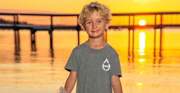 Boy holding trash by the beach