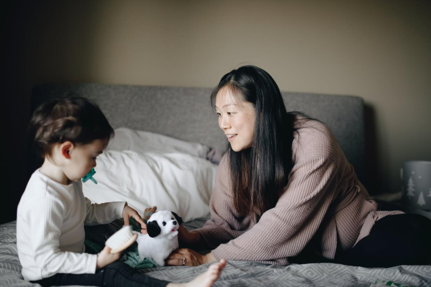 mom with her son playing with stuffed dog